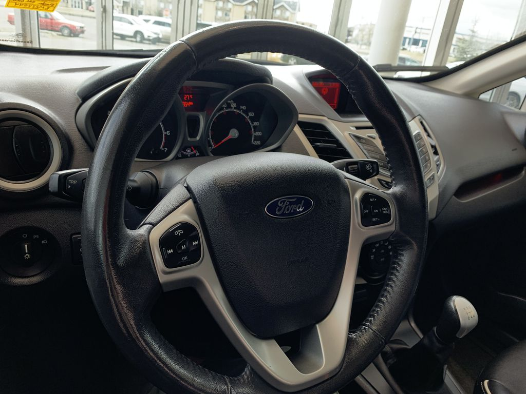 Green[Lime Squeeze Metallic] 2011 Ford Fiesta Steering Wheel and Dash Photo in Edmonton AB